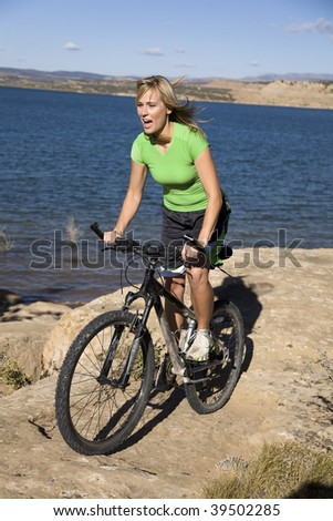 A woman having fun bike riding on a rock by the water.