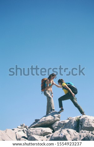 A woman helps her friend climb a stone. Helping hand. Two girls with backpacks travel together.