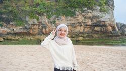 A woman hijab play water in beach, Drini beach, Yogyakarta