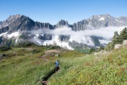 A Woman Hiker among Rocky Mountains on the Cascade Pass Sahale Arm Trail North Cascades National Park, Washington.