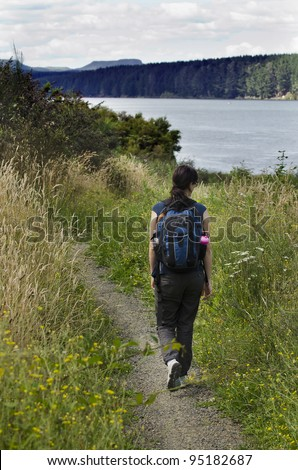 A woman hiking in the nature near a lake. Concept photo of women freedom, travel, vacation ,happy, happiness, solo, alone, single, fun.