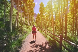a woman hiking on a beautiful foot path in a forest of aspen trees deep in the mountains.