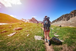 a woman hiking on a trail high in the mountains with a backpack and hiking poles