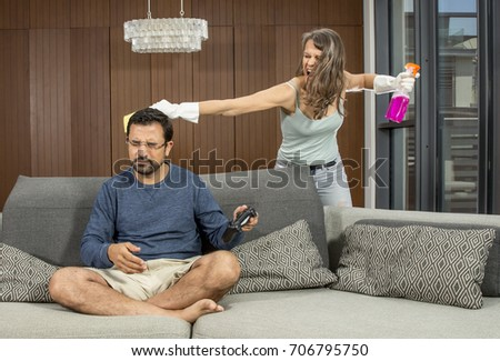 a woman hitting a man with a cleaning cloth while he is playing a video game