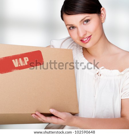 A woman holding a box inside office building or home interior. Package sign on box