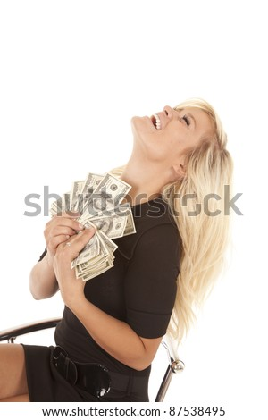 A woman holding a bunch of money leaning back in her chair laughing.