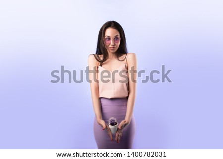 A woman holding a cactus in her hands in the bikini area. The girl depicts the discomfort associated with irritation in the bikini area and unpleasant sensations on critical days. #1400782031