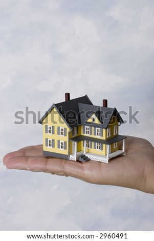 a woman holding a house in her hand  with copy space fro your message
