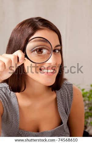 A woman holding a magnifying glass in front of her eye and looking at the camera