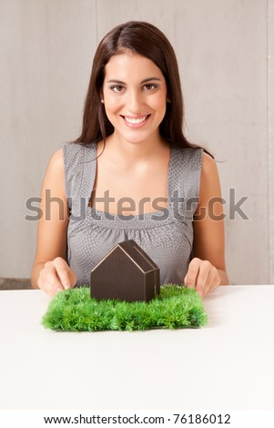 A woman holding a model house which is sitting on a turf of grass