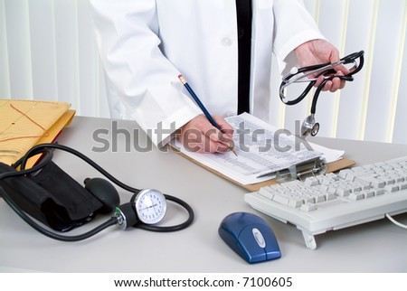 A woman holding a stethoscope; standing by a desk with a blood pressure cuff laying on it.