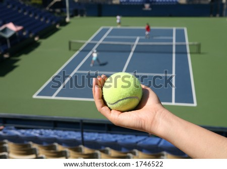 A woman holding a tennis ball with a match in the background