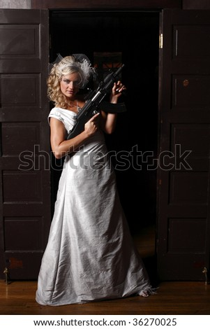 A woman holding an assault rifle safely with her finger off the trigger.