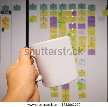 A woman holding ceramic coffee cup in front of a scrum board which has colorful story cards #1233063232