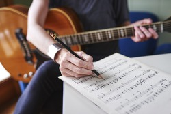 a woman holding guitar and learning to play song
