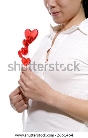 A woman holding heart lollipops isolated over white