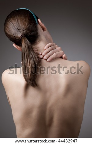 A woman holding her neck in pain with bare back