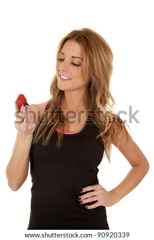 A woman holding on to a strawberry with a smile on her face.