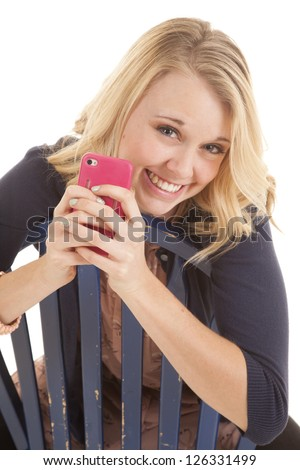 A woman holding on to her cell phone leaning over the back of a chair with a smile on her face