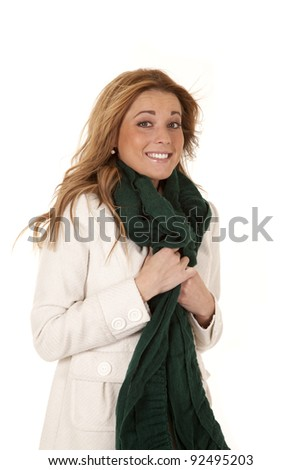 A woman holding on to her coat and scarf with the wind blowing her hair with a smile on her face