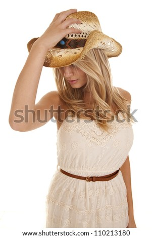 A woman holding on to her cowgirl hat looking down.