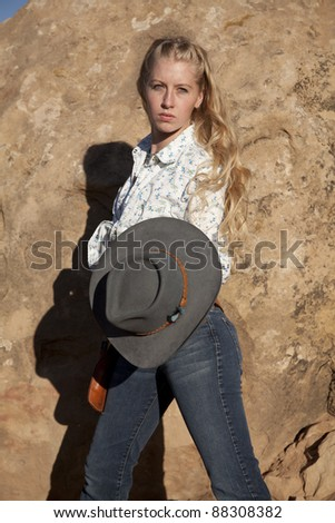 a woman holding on to her cowgirl hat with a serious expression on her face.