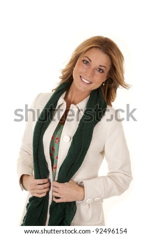 a woman holding on to her scarf with a smile on her face. - stock photo