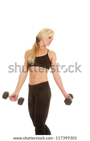 a woman holding on to her weights looking back over her shoulder