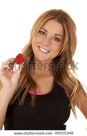 A woman holding out a strawberry in her hand with a smile on her face.