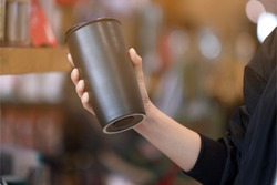 A woman holding reuse black coffee bottle in coffee cafe