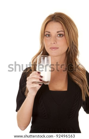A woman holding up her glass of milk with  a serious expression.