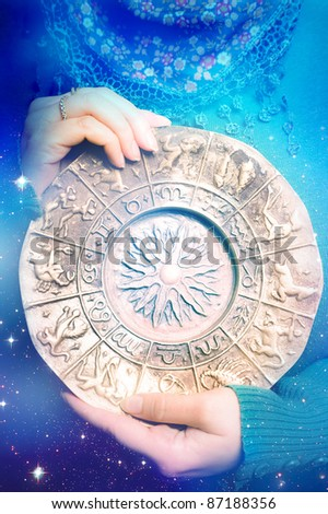 a woman holding zodiac over starry background