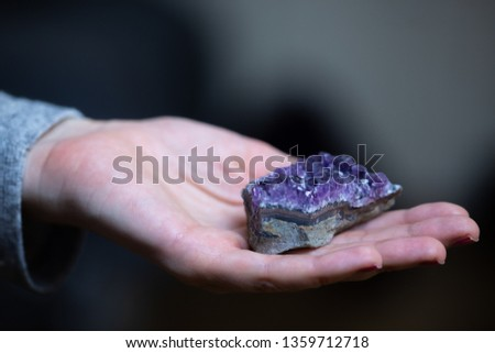 A woman holds a deep purple amethyst crystal in her hand, which has healing powers to help with physical ailments, emotional issues and in energy healing and balancing of the crown chakra.