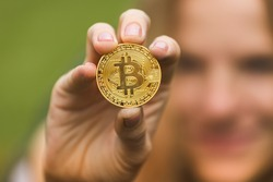A woman holds a gold coin in her hands bitcoin against a background of green grass