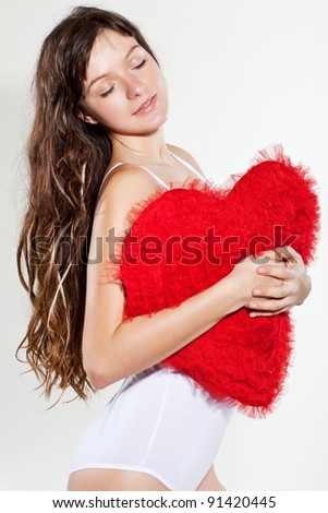 A woman holds a heart in his hands on a white background.