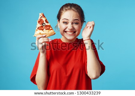 A woman holds a pizza with salami sausage and laughs gesticulating with her hands #1300433239