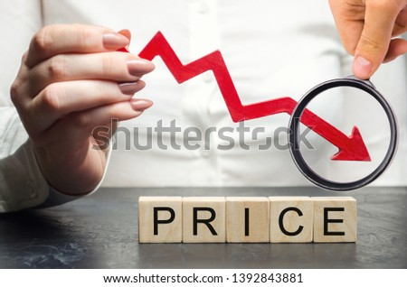 A woman holds a red arrow down over wooden blocks and the word Price. Concept of falling market value. Promotions and sale. Reduced prices for housing and food. Dumping. Low prices