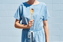 A woman holds a wooden bamboo spoon in her hand in front of her, pointing up. On a bright sunny day. Healthy lifestyle and eco friendly, reusable and recycle concept. Blue brick wall behind.