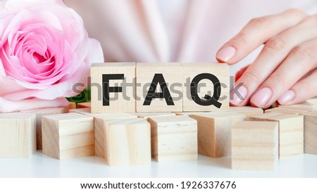A woman holds a wooden cube with the text of FAQ in her hand. On the wooden cubes there is a living rose flower. Pink background, front view. Business concept. FAQ - Frequently Asked Question Сток-фото ©