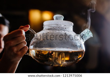 A woman holds in her hand a glass teapot in which Chinese green tea is brewed. Steam comes from the spout of the kettle