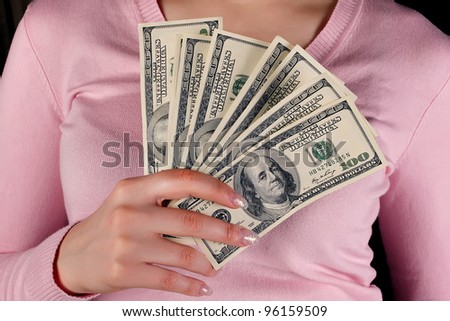 A woman holds in the hands of dollars
