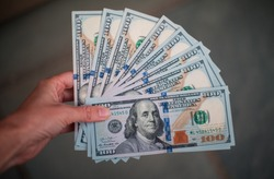 A woman holds 1,000 US Dollars in the form of ten 100 Dollar bills.