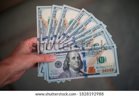 A woman holds 1,000 US Dollars in the form of ten 100 Dollar bills. Stock photo ©