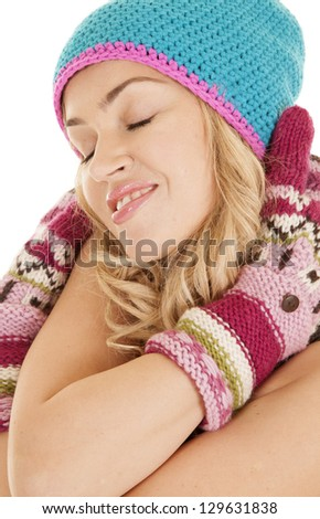 A woman hugging herself while wearing her warm mittens and hat.