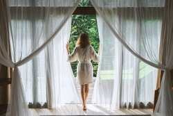 A woman in a bathrobe opens the curtains in deluxe Bali hotel room overlooking the terrace and tropical trees.Woman is awoke and standing before window. Girl is opening curtains and meeting sunrise
