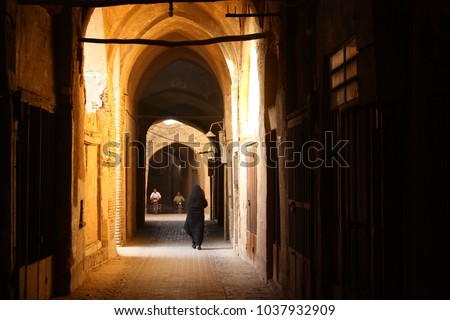 A woman in a black chador walking through the sunlit historic adobe hallways of the ancient covered Bazaar in Yazd, Iran. Two men on motorbikes are driving torwards her.  #1037932909