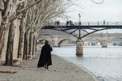 A woman in a black coat is walking along the Seine embankment.