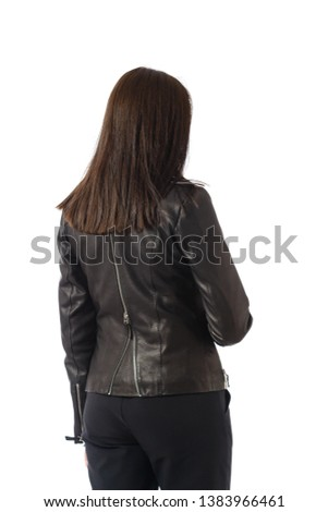 A woman in a black jacket stands back, brunette girl's back in a dark jacket isolated on white