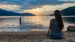 A woman in a blue dress sitting at the shore of Millstaettersee lake and enjoying the sunset. The sun is setting behind high Alps. Calm surface of the lake reflects the orange sky and the mountains.