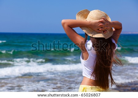 a woman in a bonnet is looking at the sea